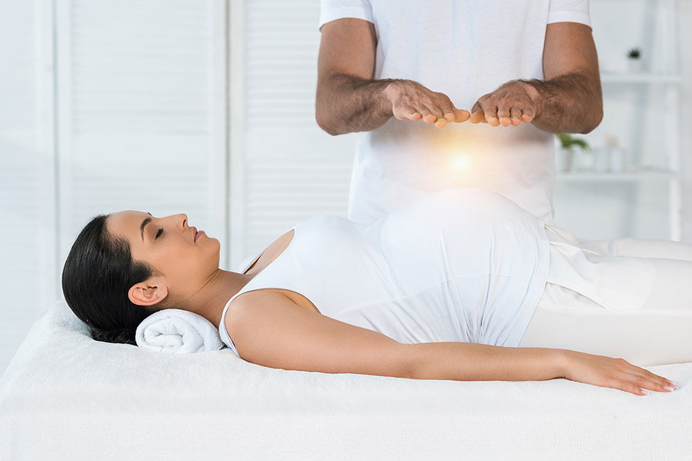 cropped view of man healing attractive pregnant woman lying on massage table